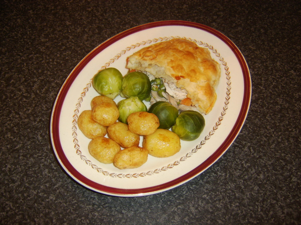 Chicken and mushroom pie served with Brussels sprouts and roast potatoes