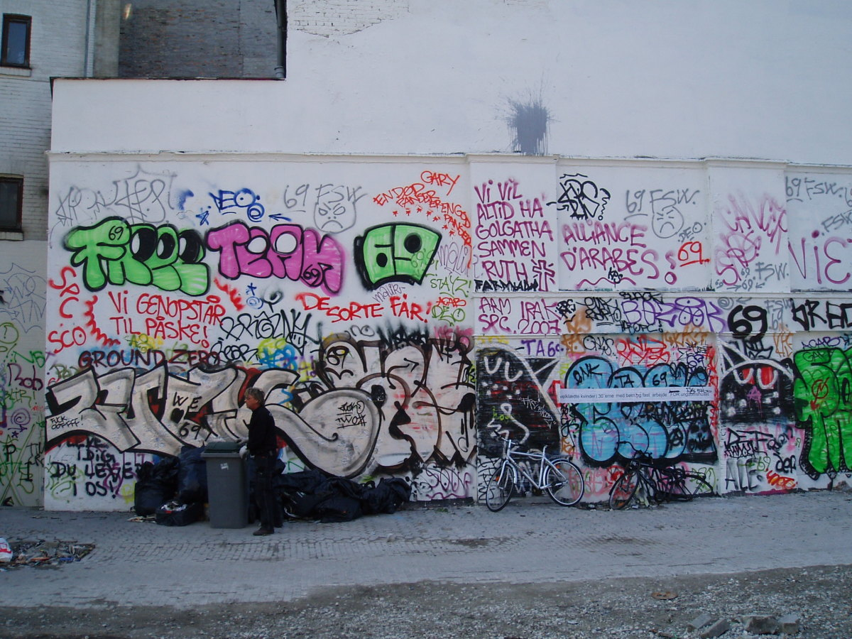 A lot of graffiti tagged on a wall, a possible indication of an unsafe area.