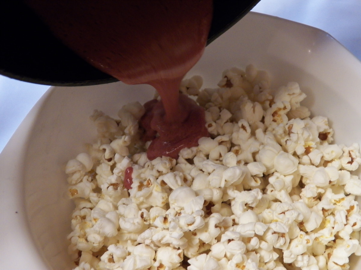 Pour flavor on popcorn in a bowl.