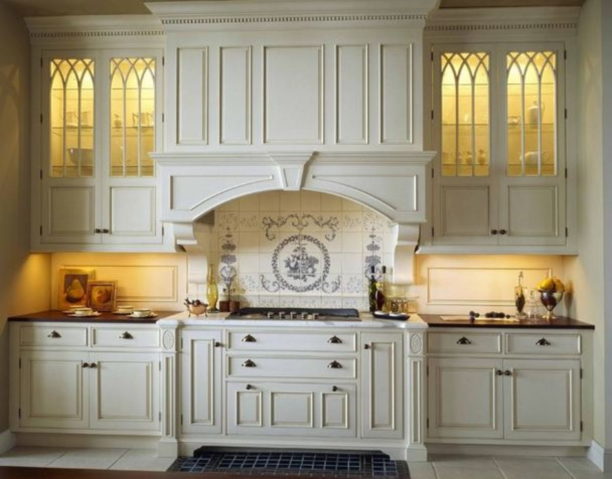 white Victorian kitchen with lighted glass cabinets and extensive moldings