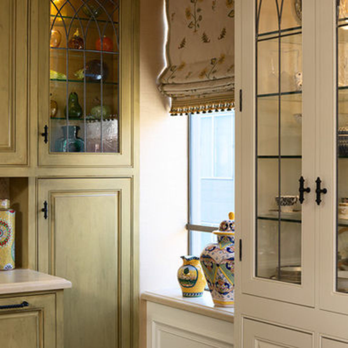 High quality brass knobs combined with glass cabinets add an Old World touch to the sage green and white cabinets