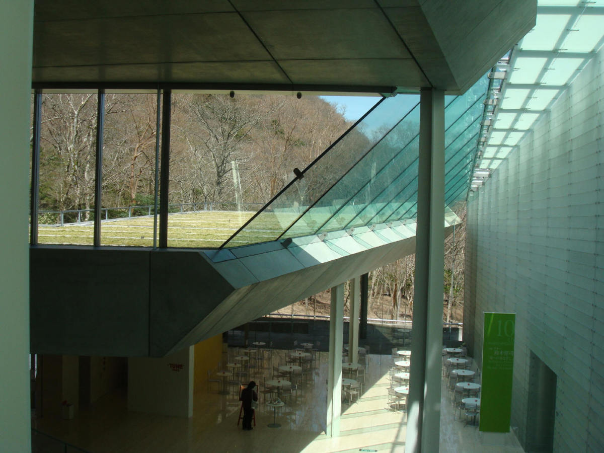 Photo taken from the ground level, captures one floor down featuring the cafe, and the roof of the structure, all grassy, is clearly visible through the glass.