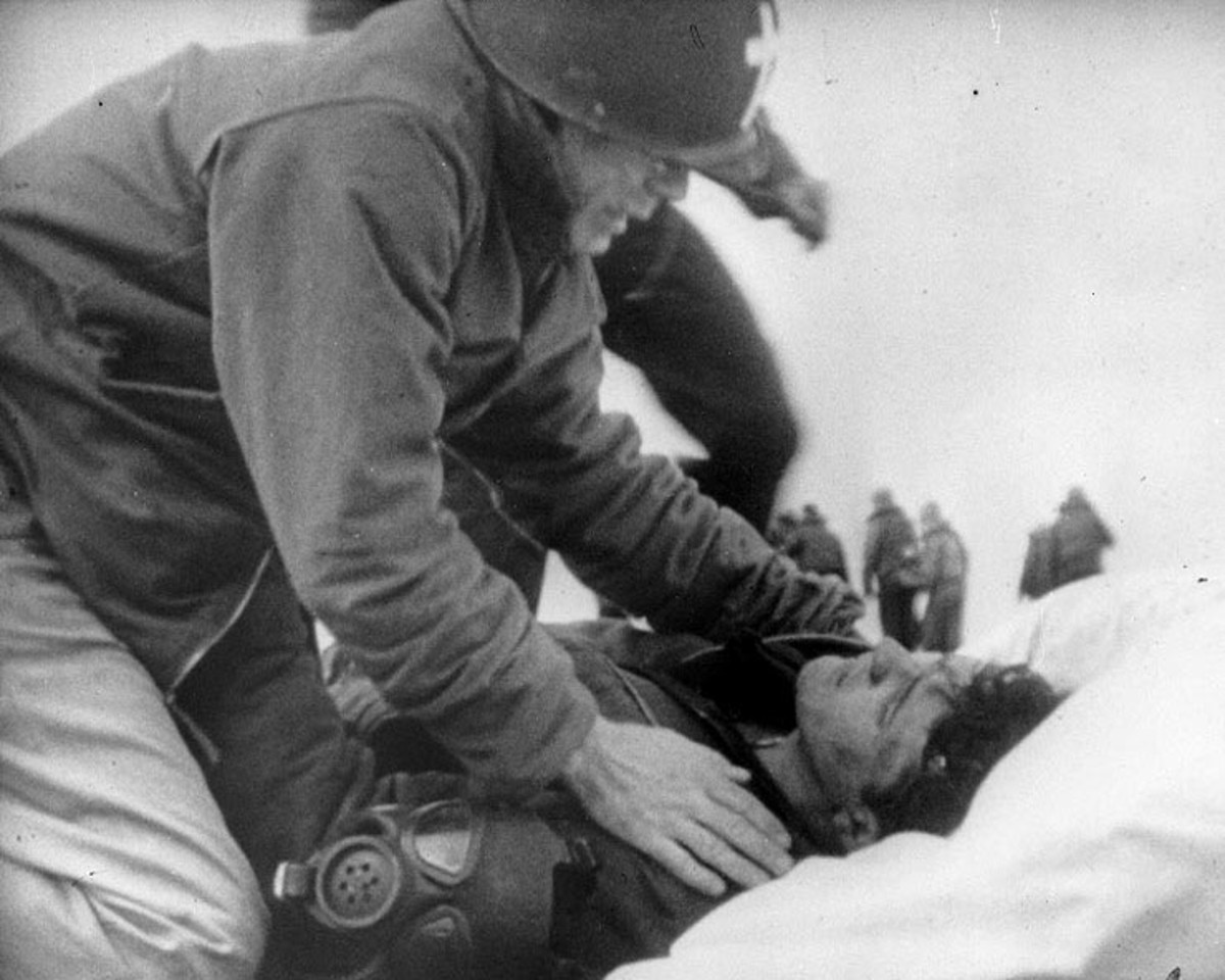 "Lieutenant Commander Joseph T. O'Callahan, USNR gives ""Last Rites"" to an injured crewman aboard USS Franklin, 19 March 1945. The crewman is reportedly Robert C. Blanchard, who survived his injuries."