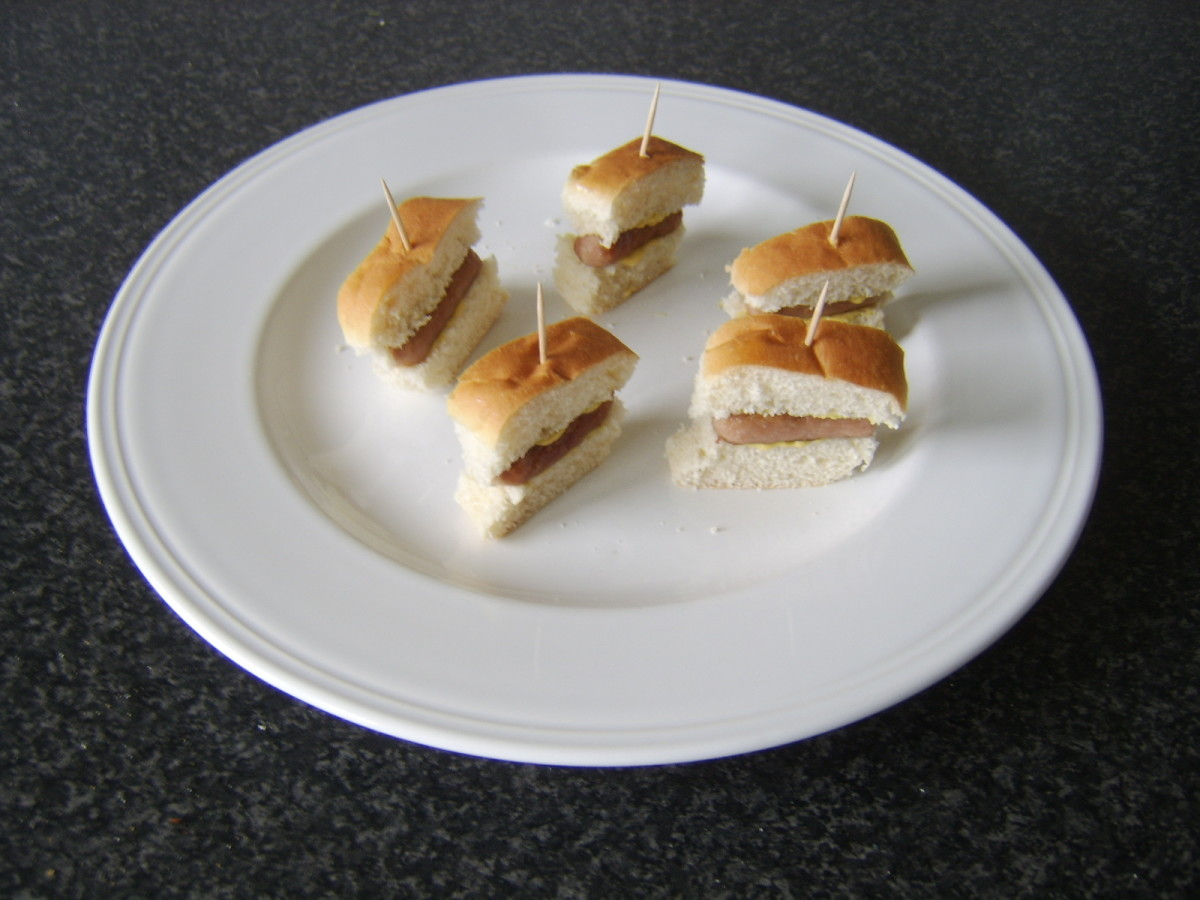 Cocktail sausages are skewered between two mustard spread pieces of a small sub roll