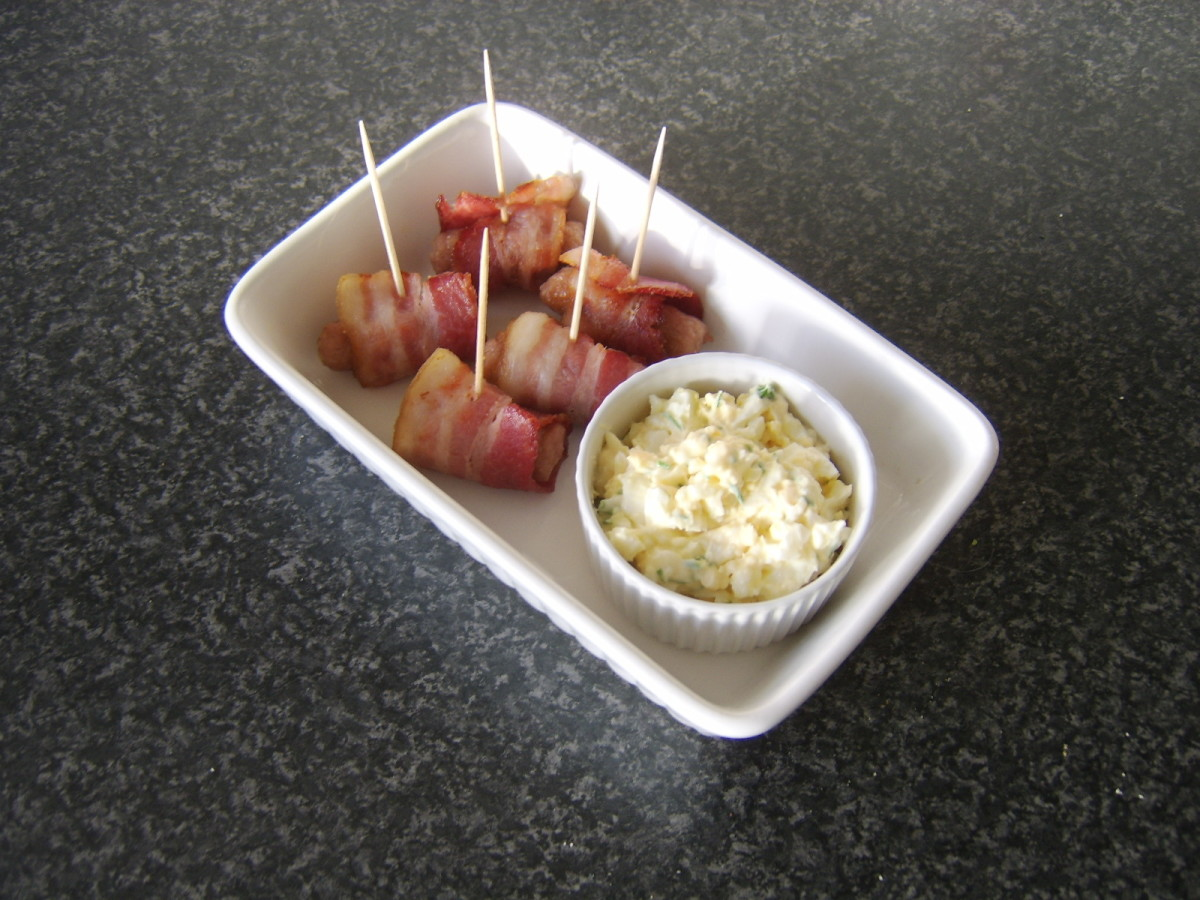 Cocktail sausages are wrapped in bacon and served with an egg mayo dip