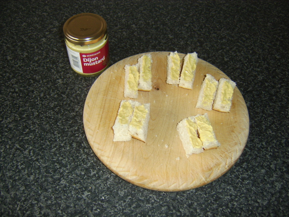 Dijon mustard is spread on the sub roll pieces