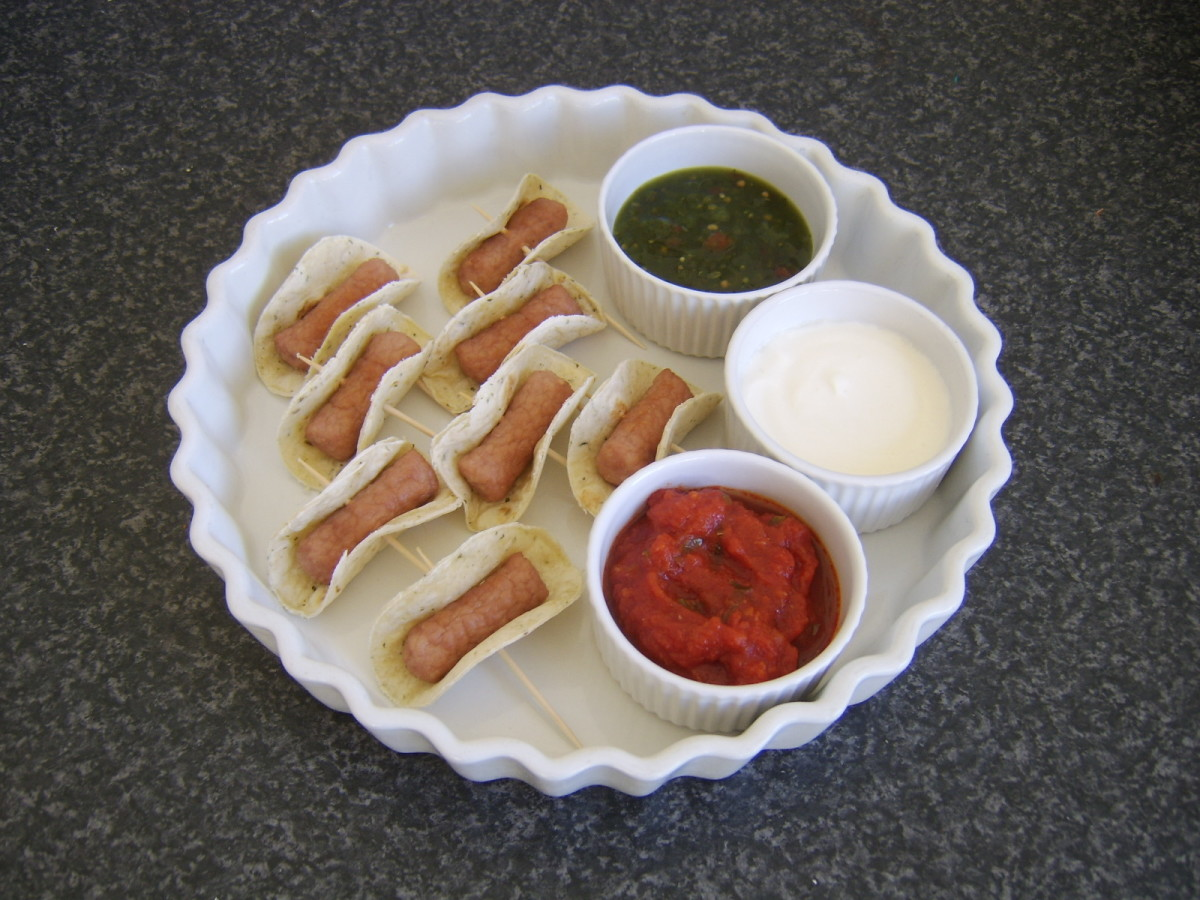 Cocktail sausages are wrapped in circles of tortilla and served with a selection of dips