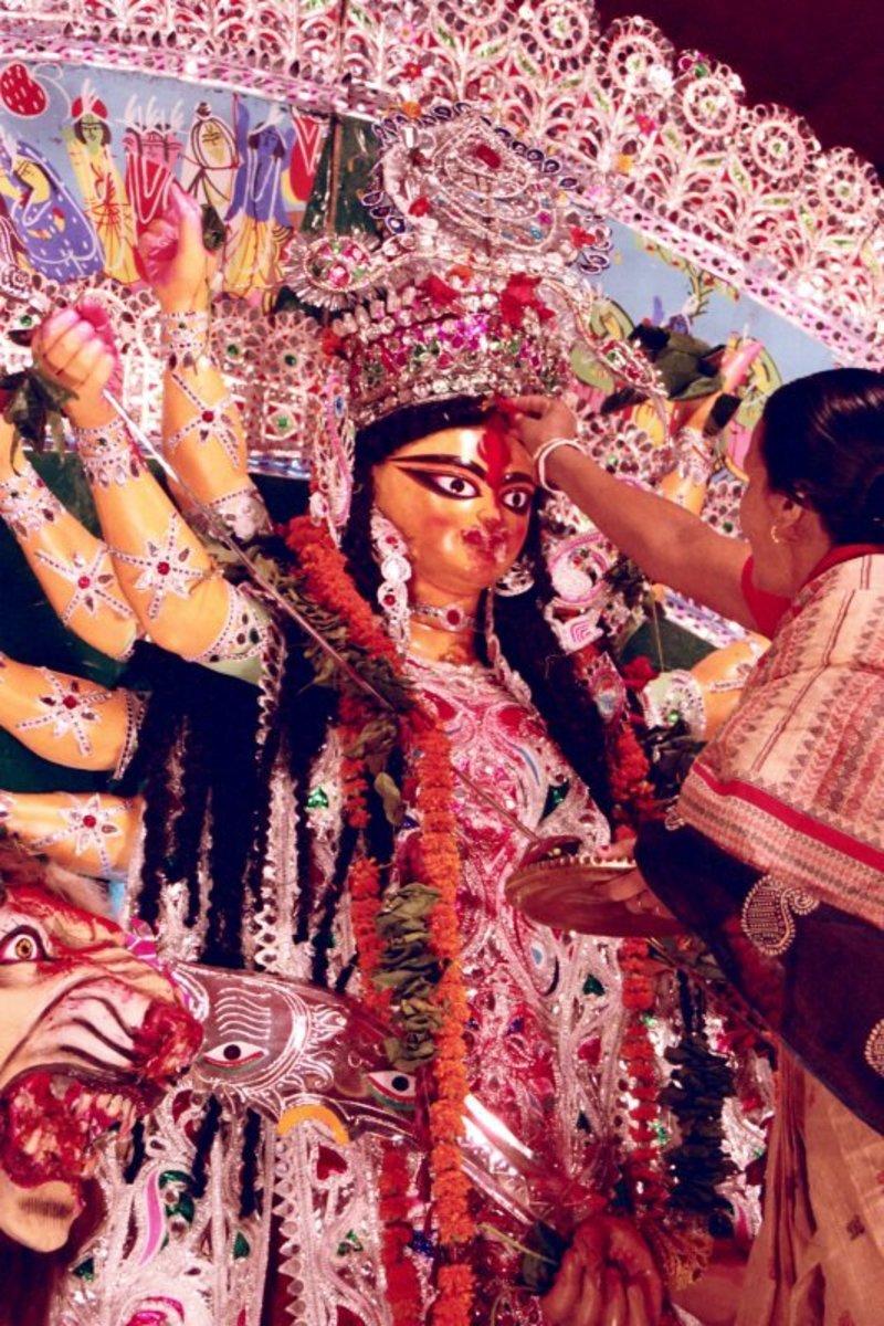 Sindur or vermillion being applied to Goodess Duga on Dashmi day