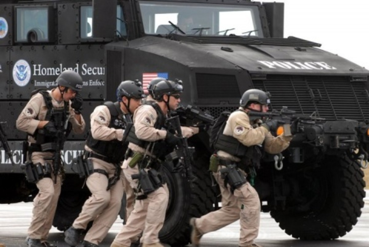 Four agents  ICE training. Using posture with their massive armored truck.