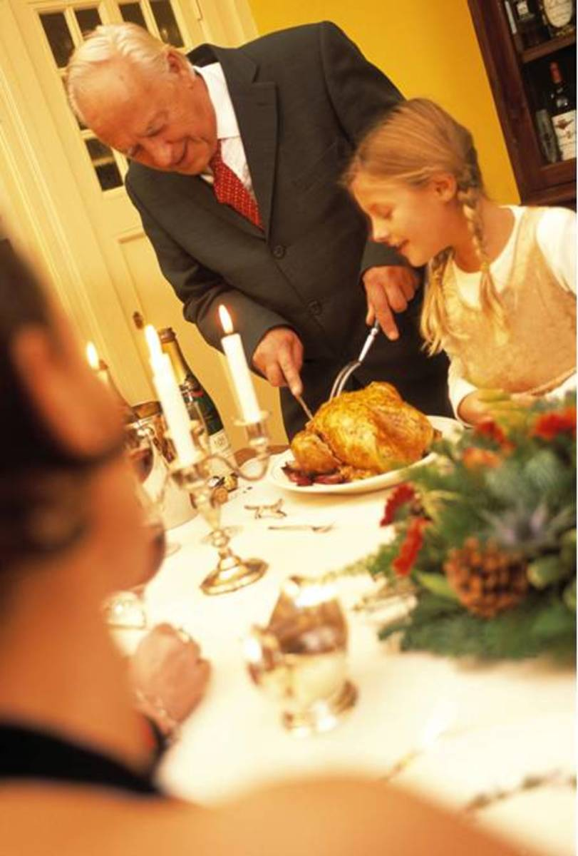 Grandfather Carving Thanksgiving Turkey at Dinner Table