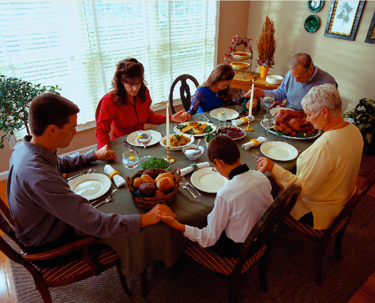 Modern Family Praying at Thanksgiving Dinner Table