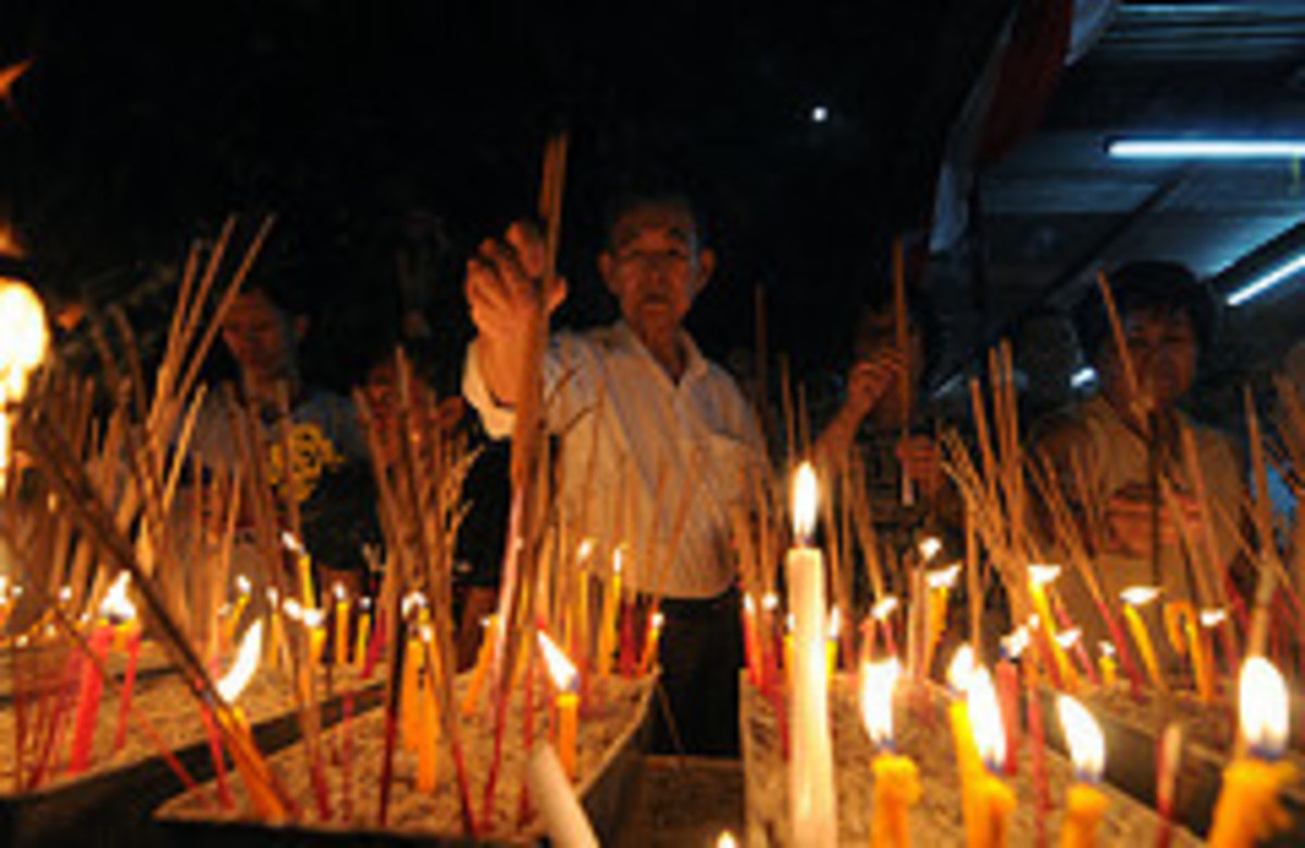 Lighting candles and joss sticks on Wesak day