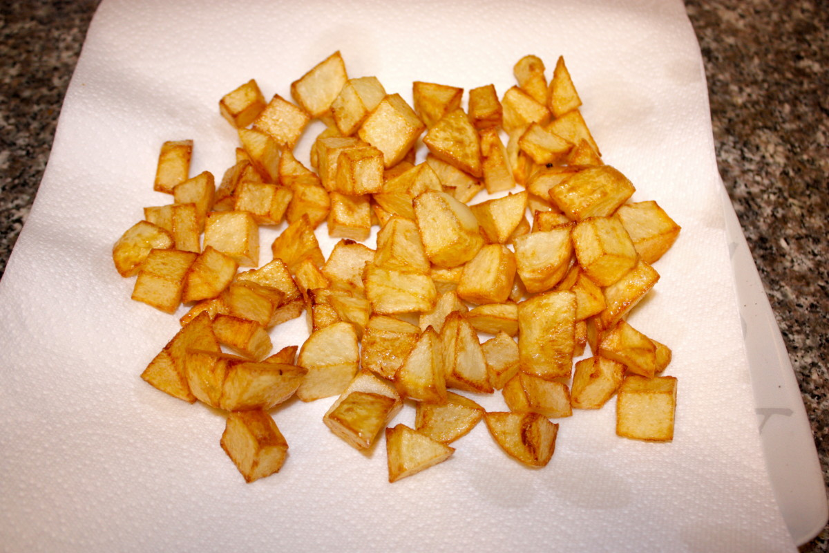 Cooked potatoes draining on a plate covered in paper towels (Step 2).