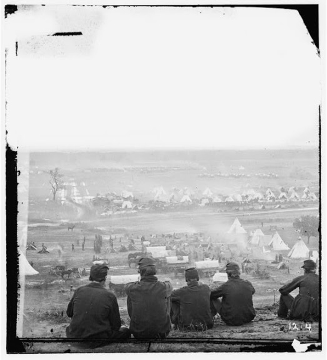Troops lounge on a hillside above a Union Army camp in the field