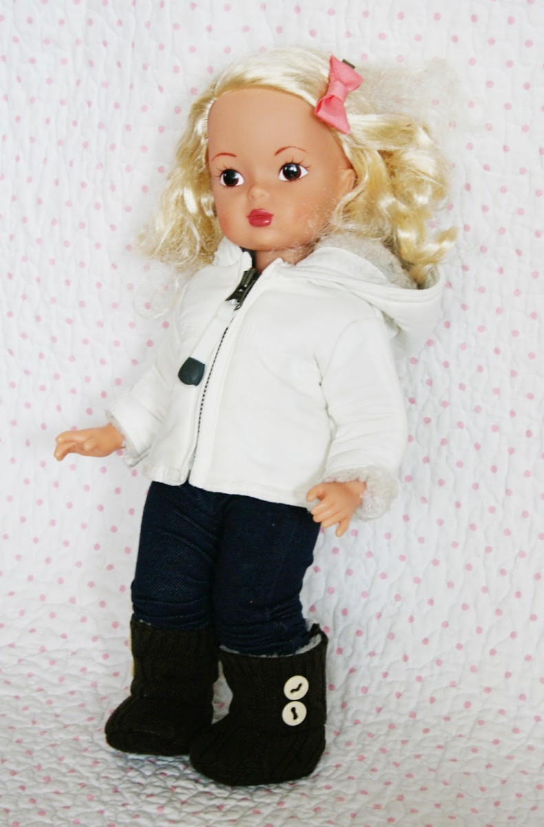 blonde doll with black pants white hoodie and tan UGGs