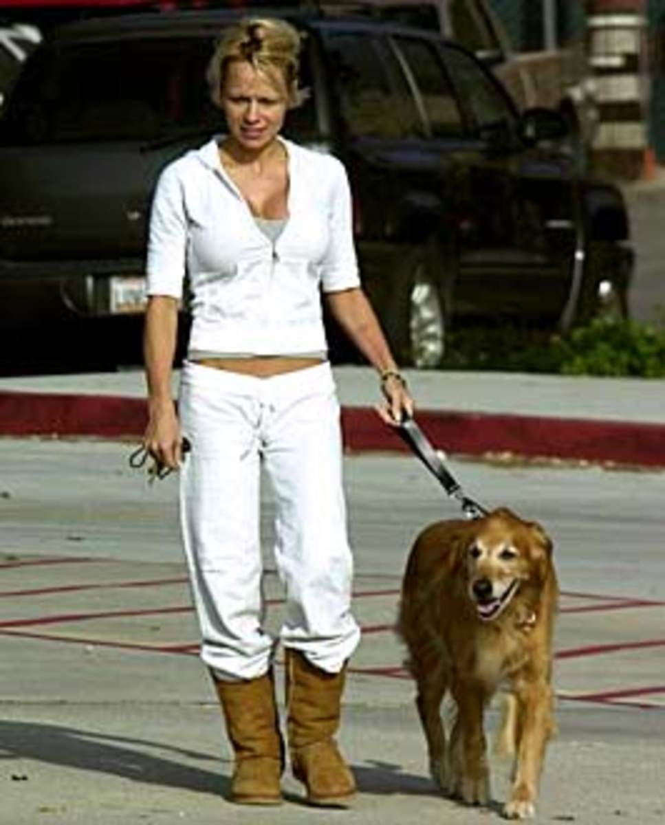 Angela Simmons walking her dog wearing white sweat pants and Uggs