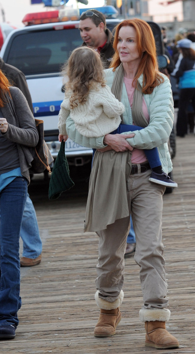 Marcia Cross in Uggs carrying her daughter