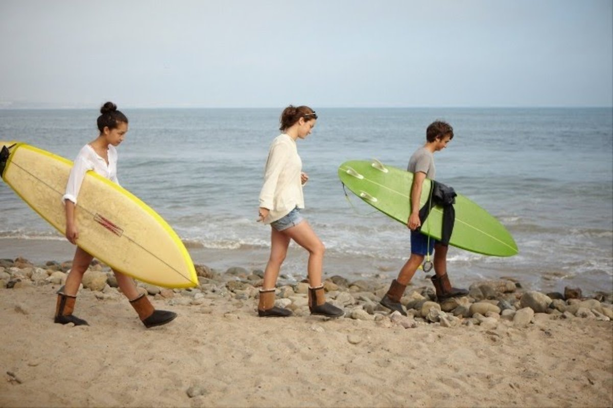 three surfers wearing Uggs and carrying surfboards