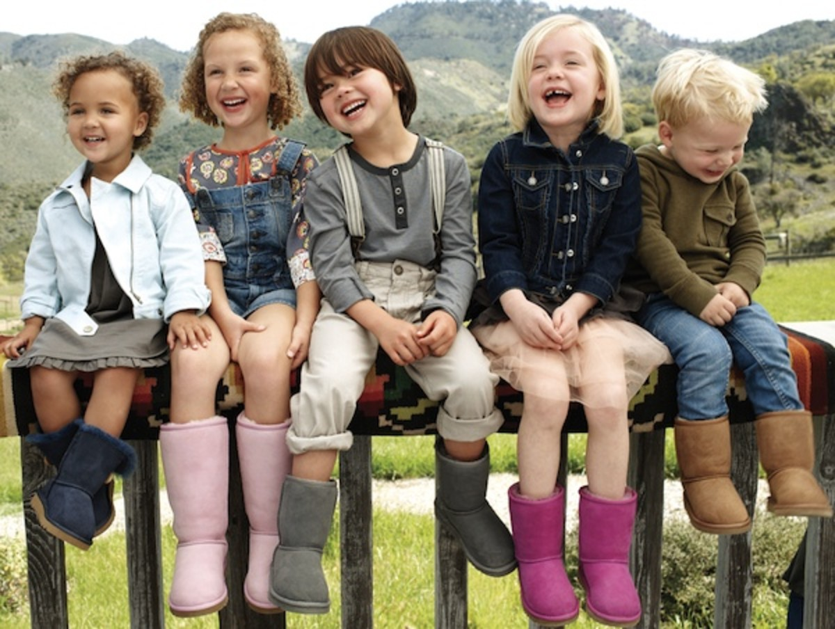 five children sitting and laughing on a bench with mountains behind them all wearing Uggs boots in different colors