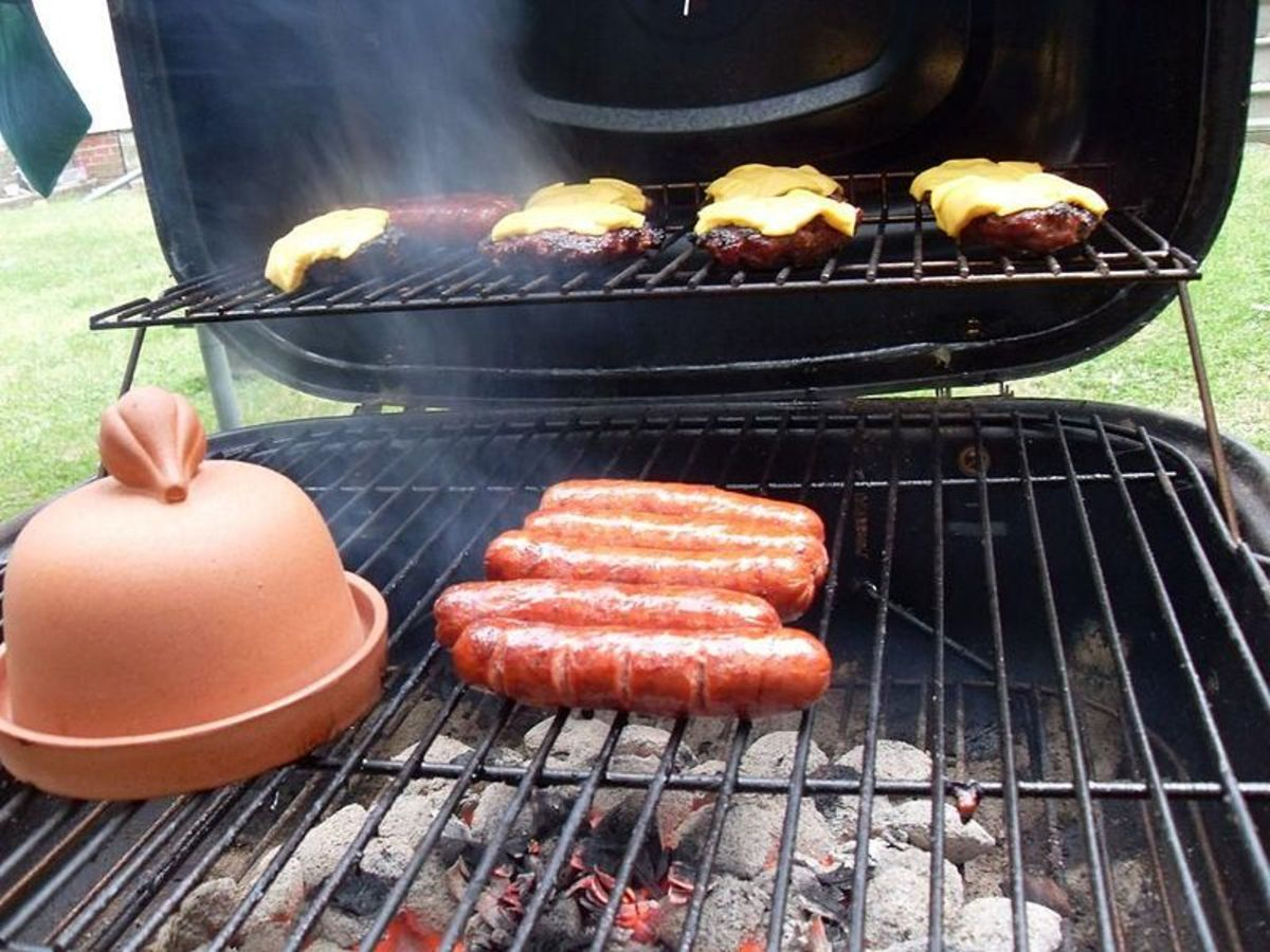 Hamburgers and hot dogs on grill, examples of fast foods.