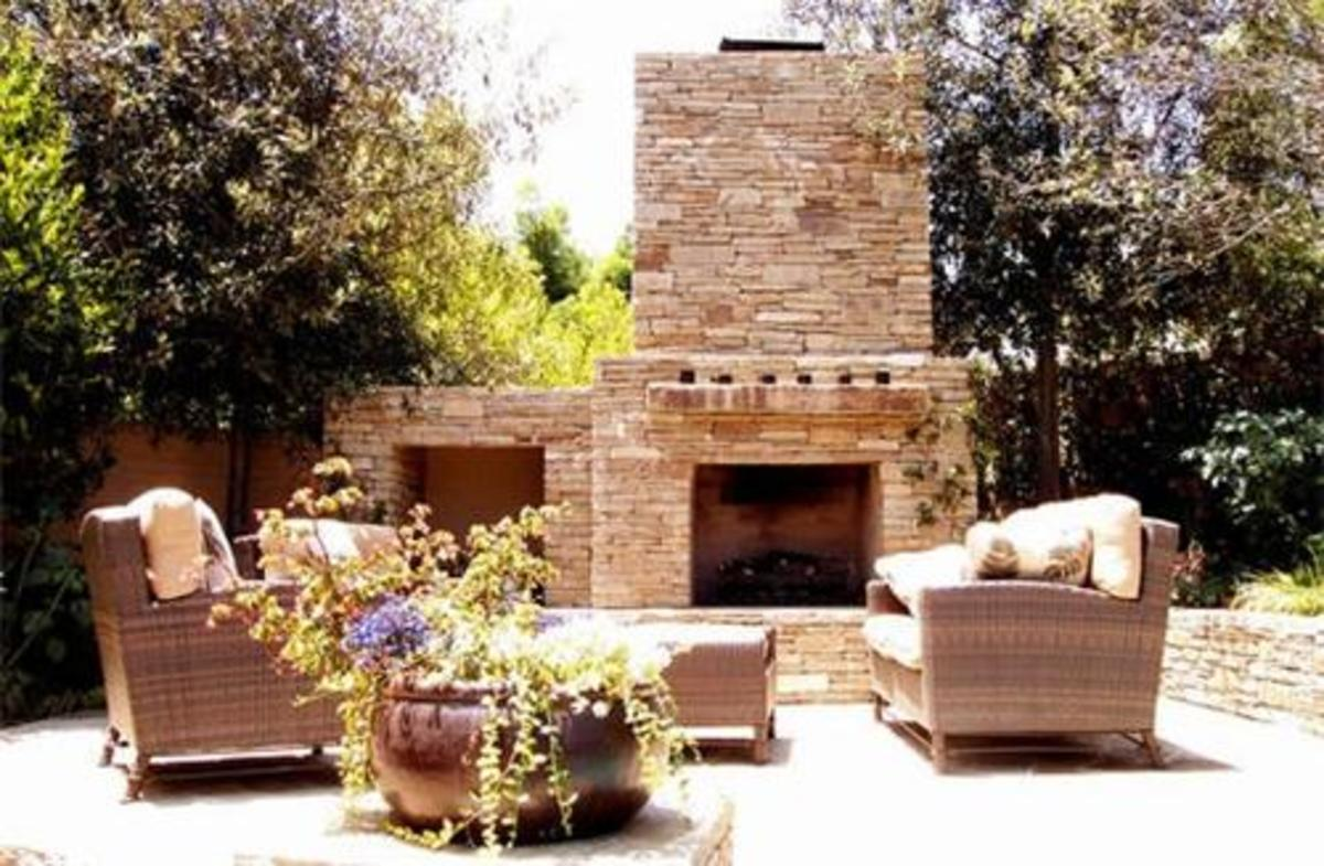 huge and very elegant stone fireplace with patio furniture in the foreground