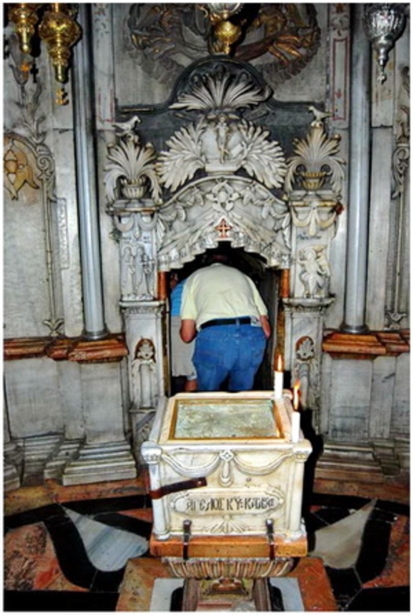 """First chamber of Jesus' tomb. The first chamber is called the """"Chapel of the Angel"""". A fragment of the covering stone of the Sepulcher is placed right behind the man who is entering the tomb."""