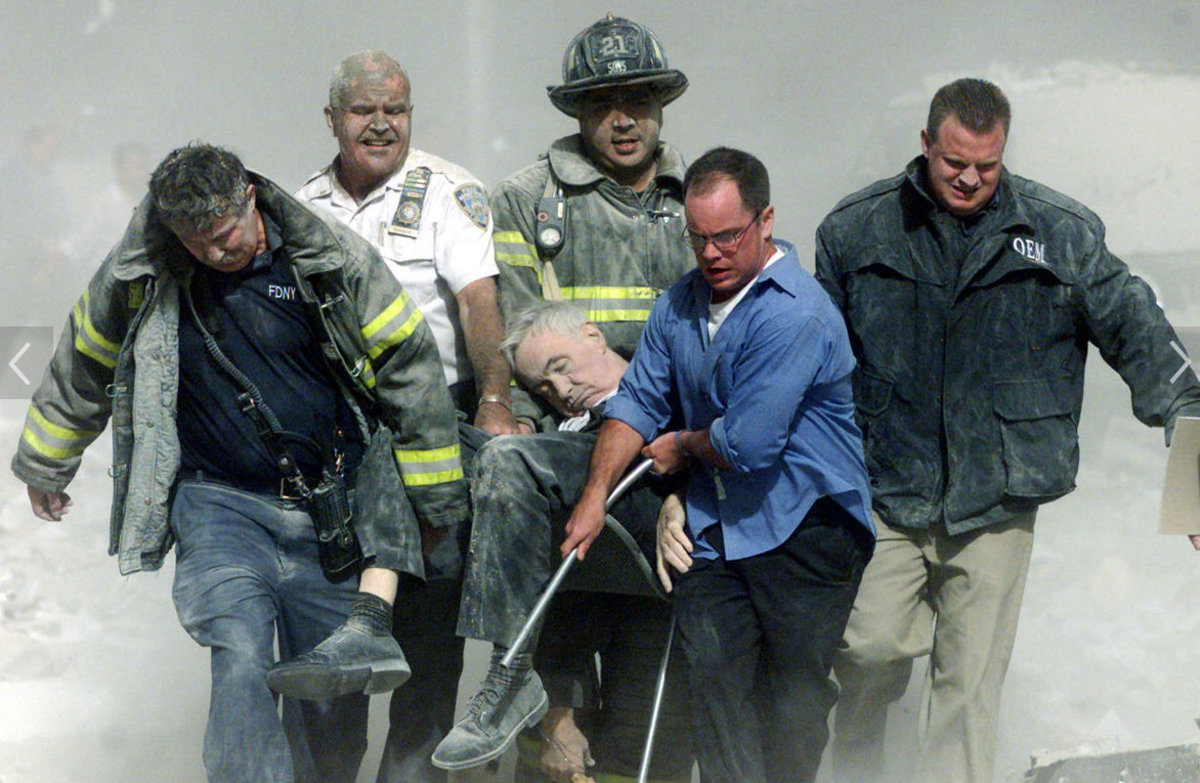 Rescue workers carry mortally injured New York City Fire Department chaplain Fr. Mike Judge from the wreckage after he was killed by falling debris while administering last rites to another victim.