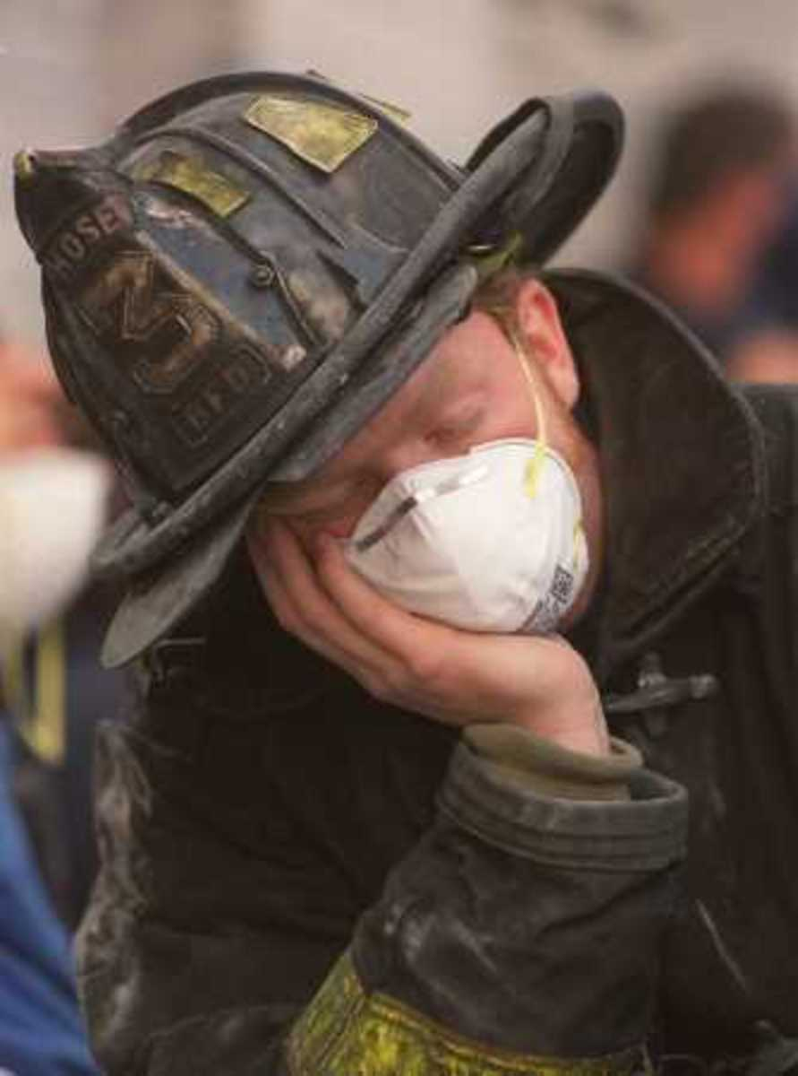 "With only a painter's mask as his ""protection,"" a weary firefighter rests his eyes ."