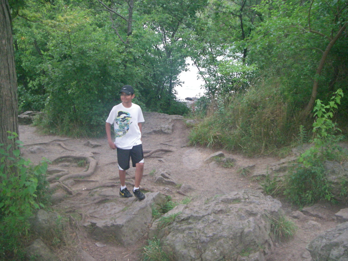 My preteen son hikes along the river.