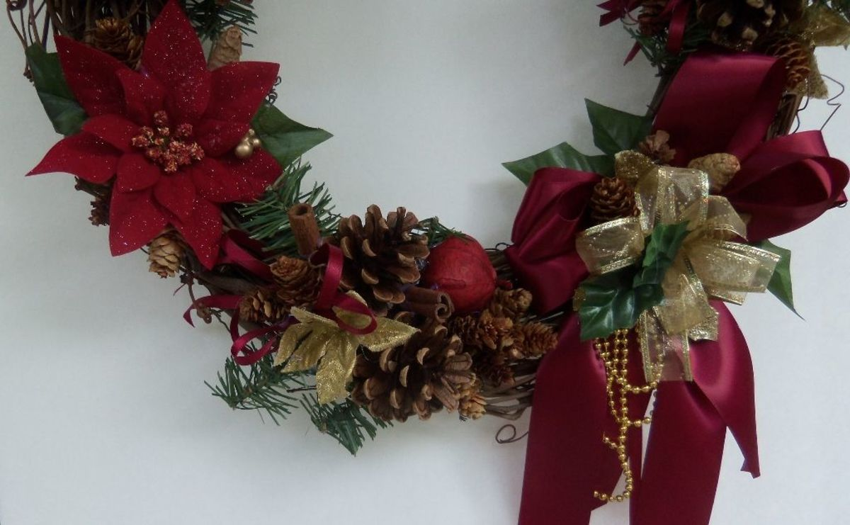"Bottom of wreath. See the 1/4"" ribbon is tucked under the gold poinsettia.  Two cinnamon pieces here."