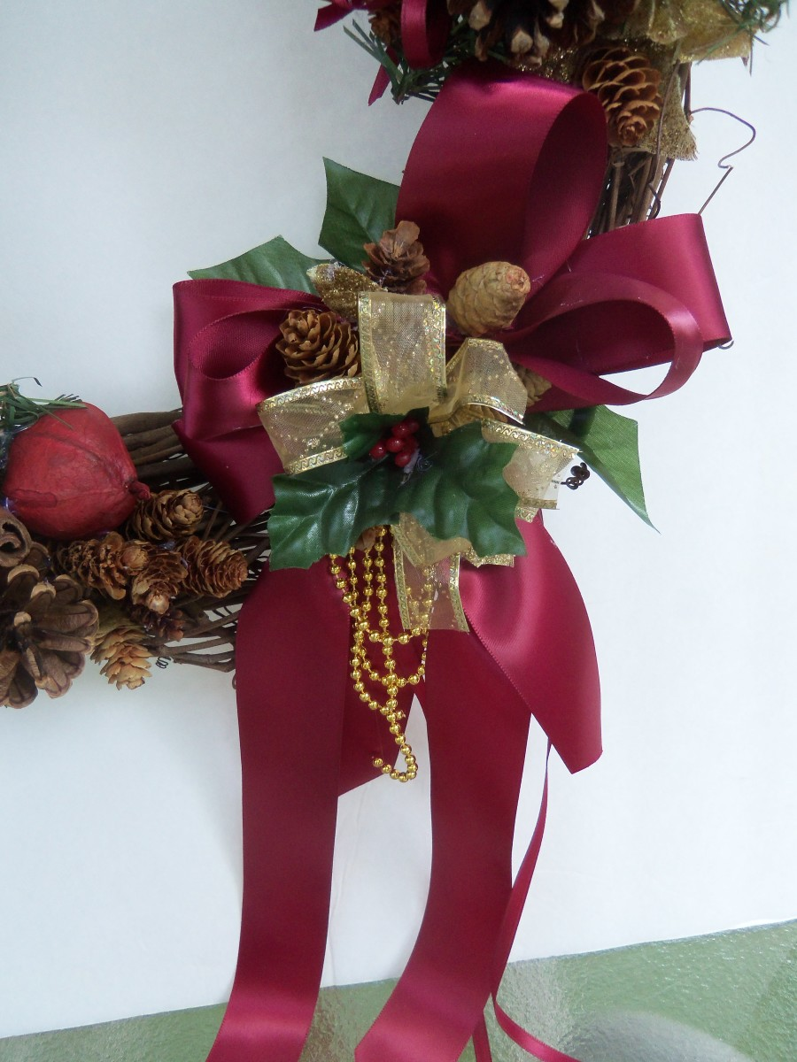 Bow at bottom of wreath. See how the gold beads have formed loops and in the center of the bow holly.