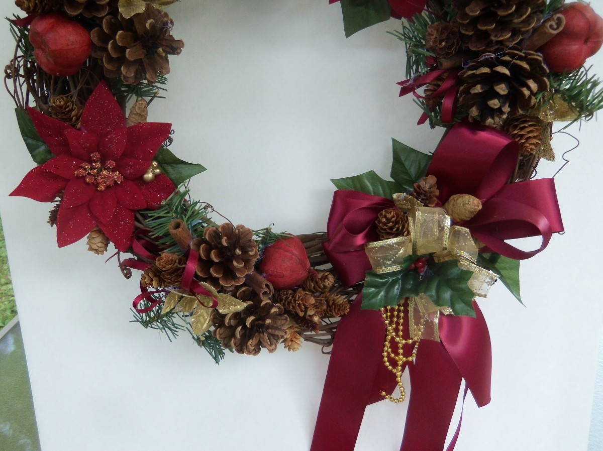 Bottom of wreath centered. Left of the bow there are 6 mini pinecones.