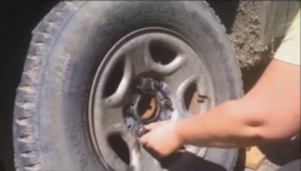 After the lug nuts are all broken free jack the vehicle up until the wheel clears the ground.
