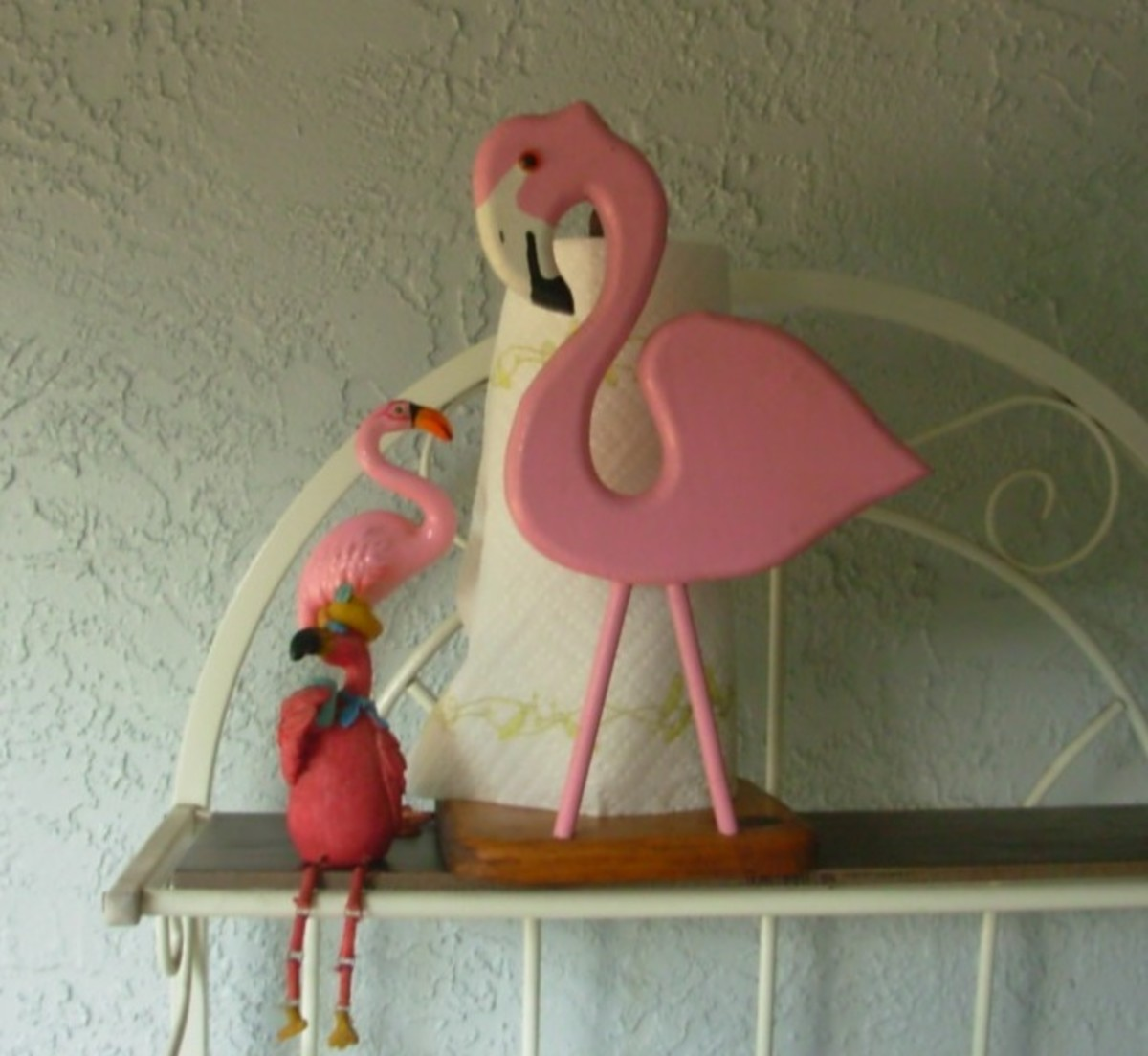 A flamingo paper towel older keeps company with a few flamingo figures.