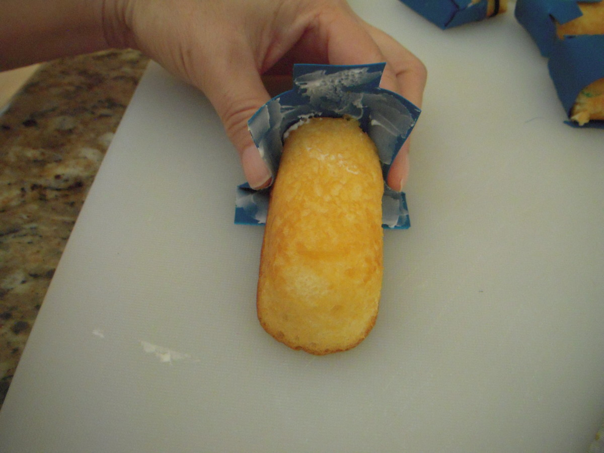 Gently press the bottom and sides of the overalls around the Twinkie. Then press the front and back of the overalls against the Twinkie. (Kind of like putting on a diaper.)