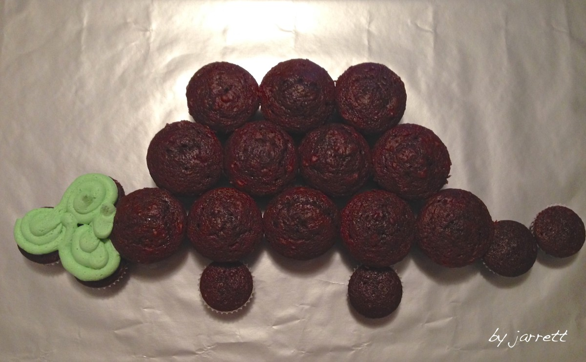 Arrange the cupcakes to resemble the outline of a dinosaur