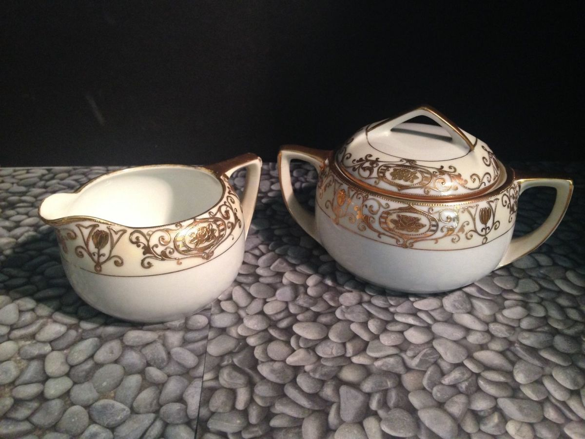 One set of cream and sugar made by the Nortake Company with the 24k gold hand painted Christmas Ball Pattern.