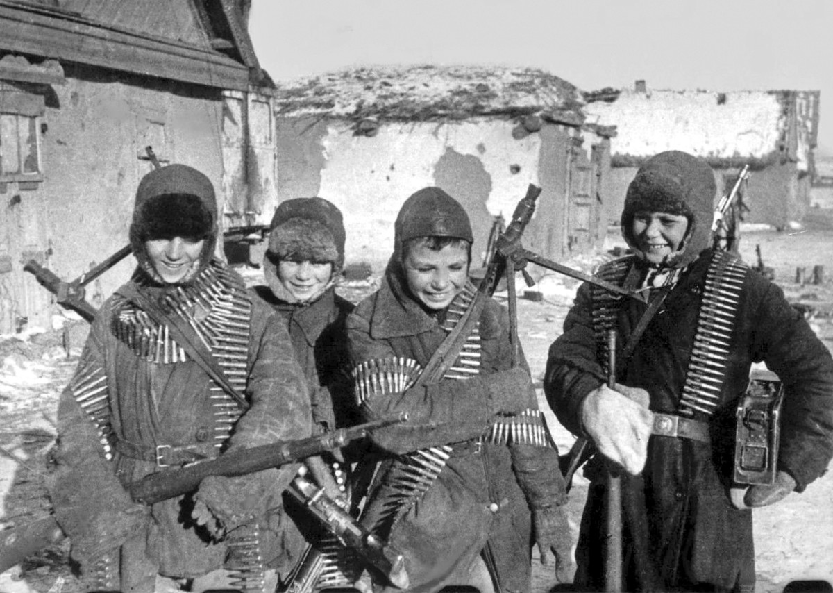 Soviet children with recently abandoned German weapons after the battle ended at Stalingrad.