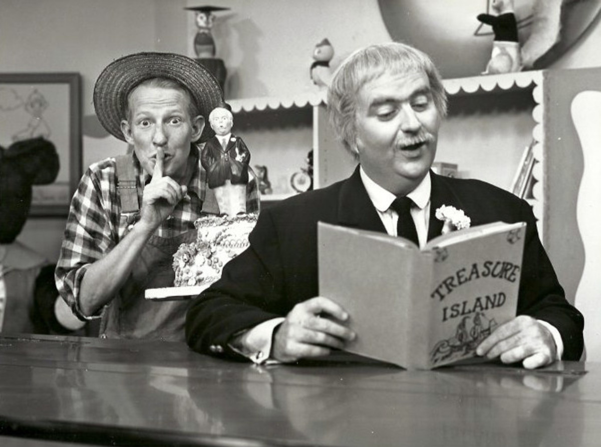 "Captain Kangaroo reading from ""Treasure Island"" while Mr. Green Jeans looks on"