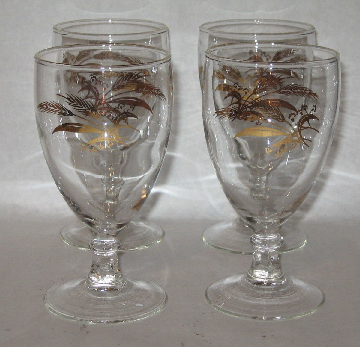 "Here are four 8 ounce water goblets they are 5-7/8"" tall with  real  24k gold accents and designs with golden wheat."