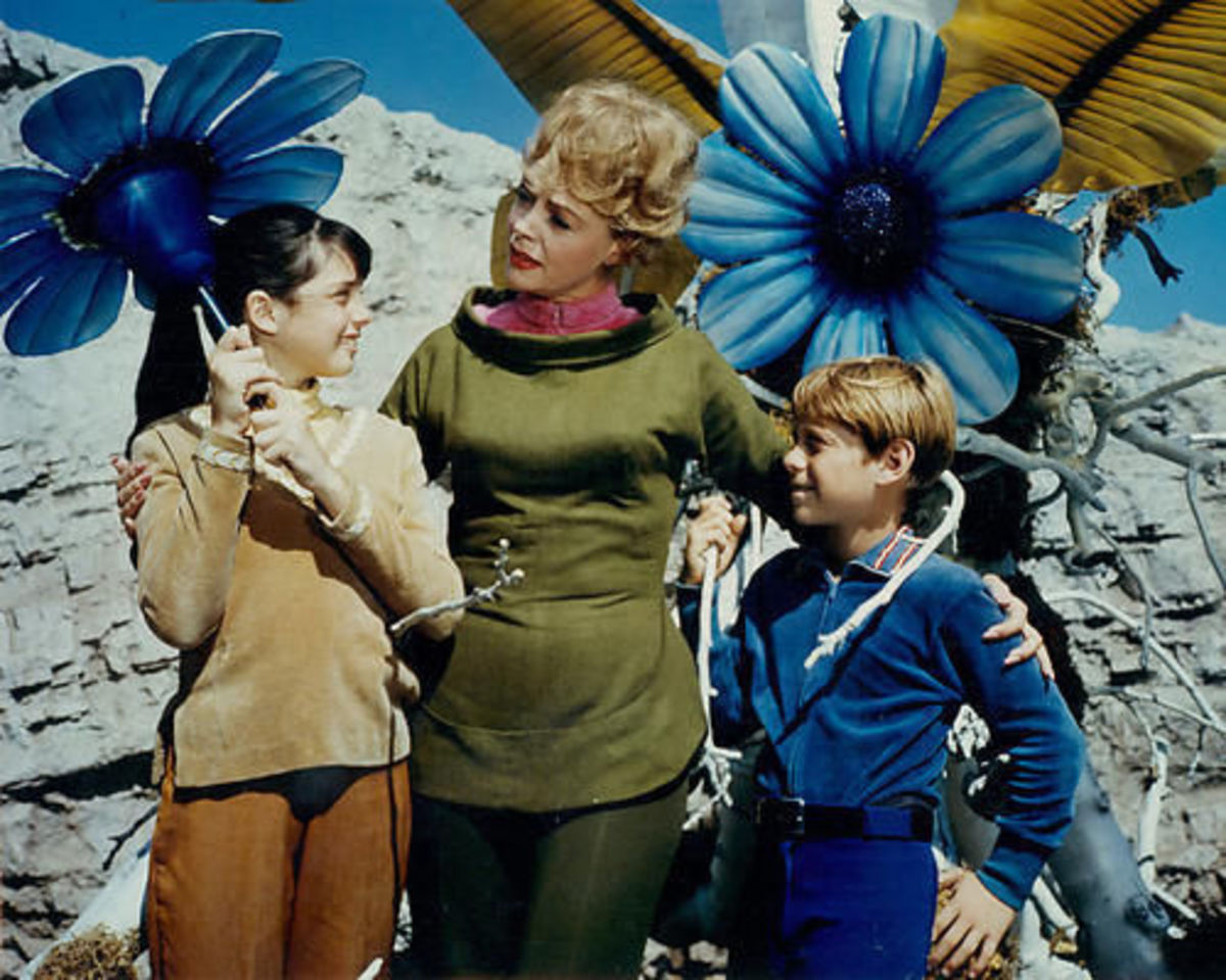 Penny Robinson, Maureen Robinson and Will with some very large flowers on a distant world made by the imagination of Irwin Allen..