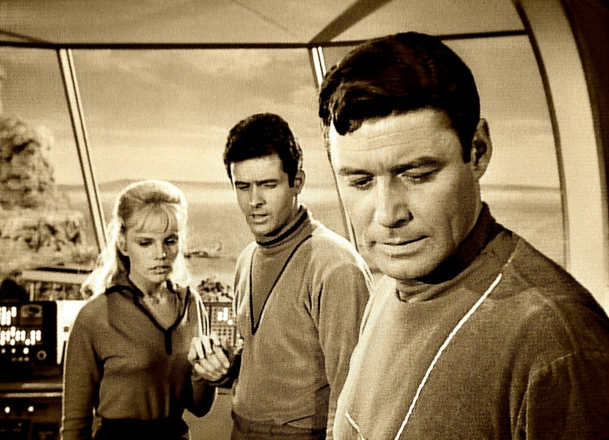 Judy Robinson, Major Don West and Professor John Robinson working on a problem in the Jupiter 2 their home and spacecraft.