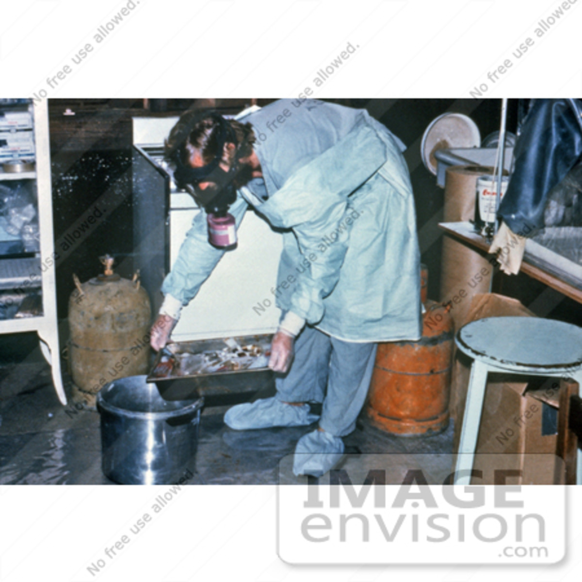 Stock photography of a heavily protected technician is shown discarding blood specimens collected during the Ebola outbreak in Zaire, 1976. Researchers hurried to identify the cause of this epidemic, pinpoint its source, and halt its spread. The dise