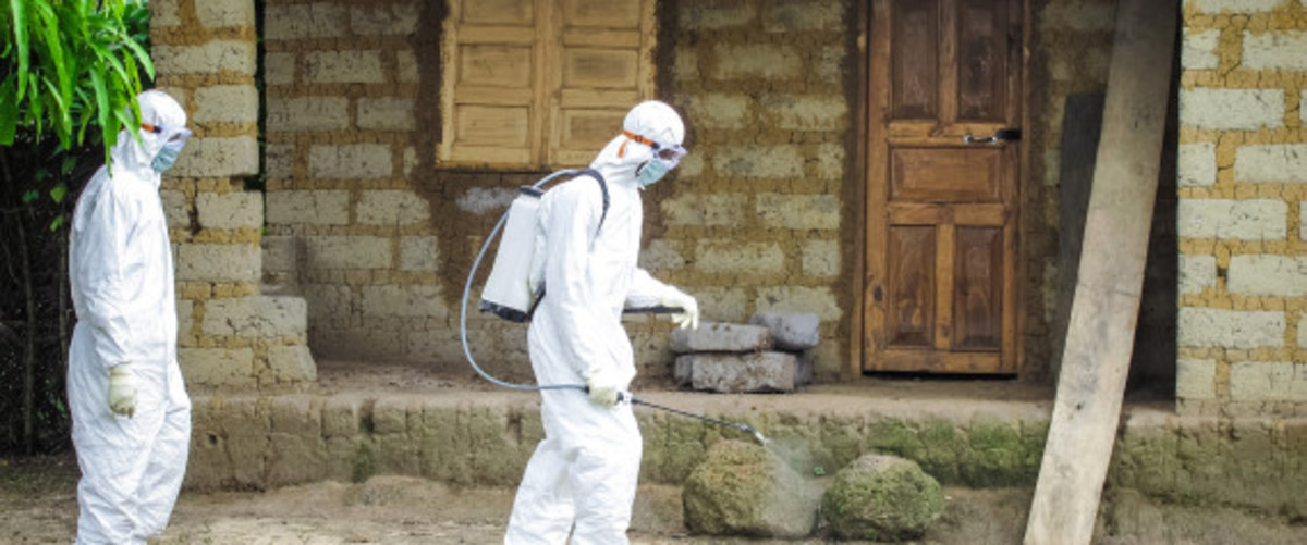 A healthcare worker in protective gear sprays disinfectant around the house of a person suspected to have Ebola virus in Port Loko Community, situated on the outskirts of Freetown, Sierra Leone, Tuesday, Oct. 21, 2014