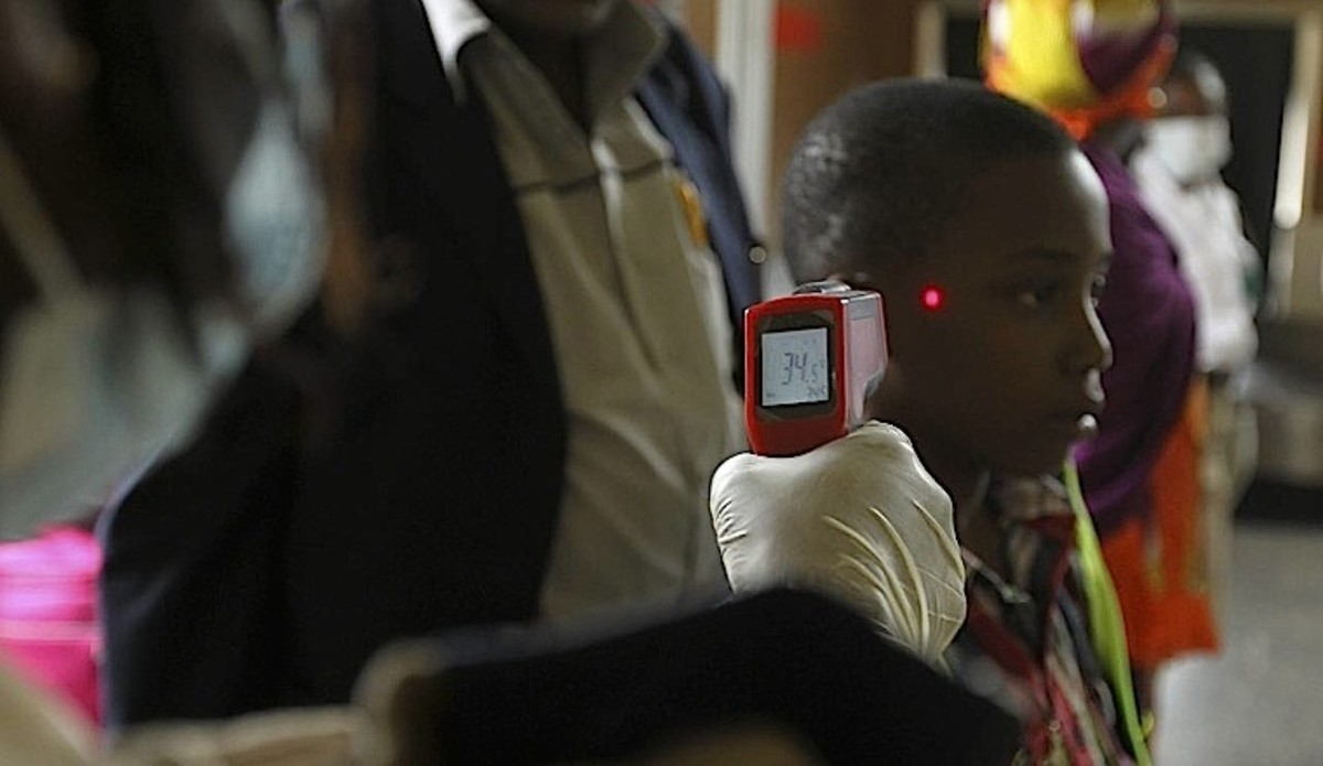 A boy's temperature is taken using an infrared digital laser thermometer at the Nnamdi Azikiwe International Airport in Abuja.