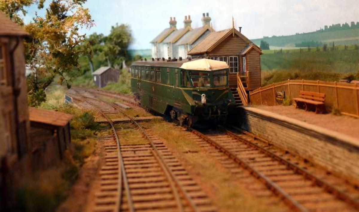 Model of an AEC GWR Railcar passing the signal box at this scale layout based on Radnor, Wales. An unusual design solution with streamlining and side fairing - for speed running?
