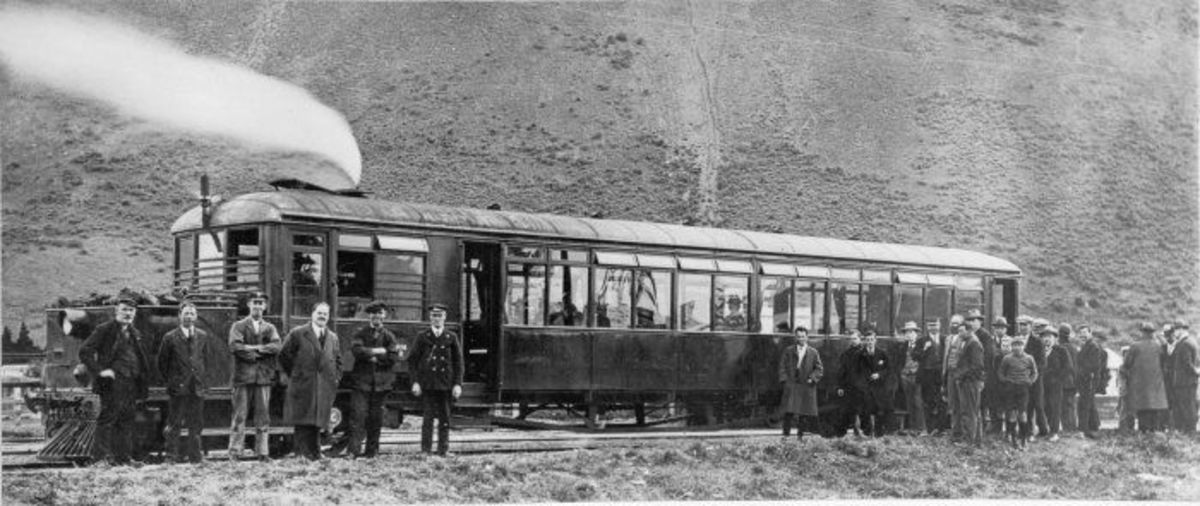 In Lincolnshire, Clayton steam railcar rests along its route wiyth passengers, crew and railway personnel at the trackside