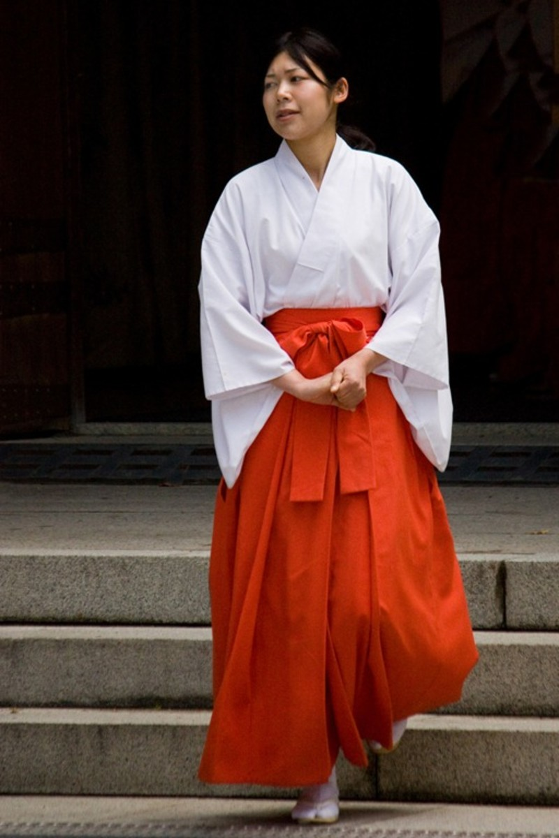 The shrine maiden, or miko, wears a white haori (kimono jacket) tucked into red hakama (trousers).