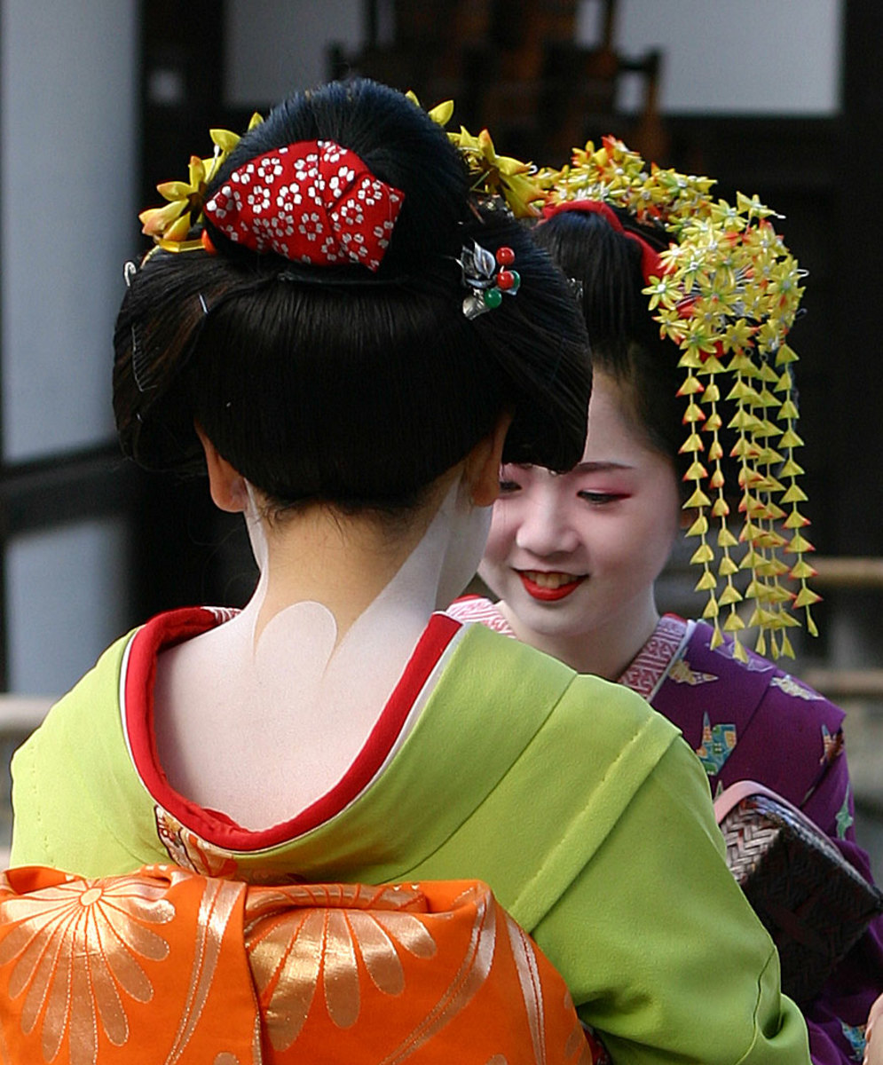 Geisha's kimonos are known for the  neckline in the back which shows off white marks on the nape of the neck. The obi in a geisha's kimono is wide and high. They wear a headdress, usually of synthetic hair, with elaborate kanzashi, or hair ornaments.
