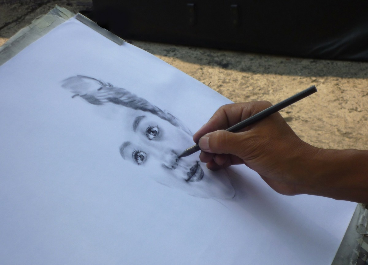 An artist busy drawing a face.